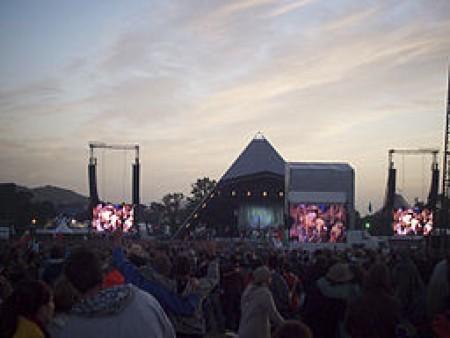 Glastonbury Festival, Pilton, Somerset The sun sets behind the Pyramid Stage. Image courtesy of Jordan Burnett via Wikimedia Commons
