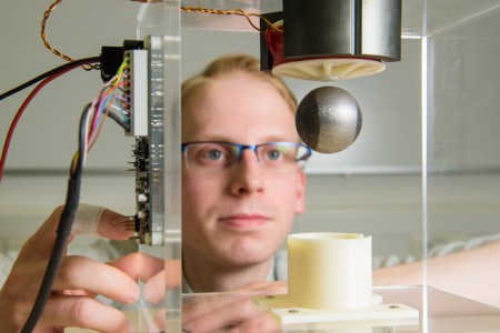 Engineer Niklas König, a member of Professor Matthias Nienhaus' research team, demonstrates the 'sensorless' technology with a steel ball (photo by Oliver Dietze)