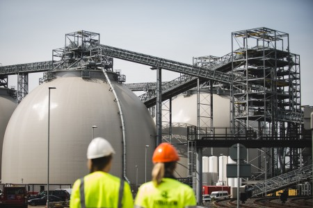 Drax biomass domes with two engineers in foreground, credit: Drax